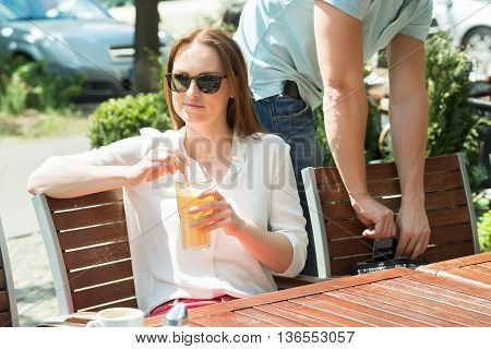 Male Thief Stealing Mobile Phone Of A Young Woman With Glass Of Juice