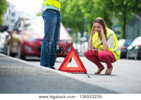 Young Worried Woman Crouching Near Triangular Warning Sign With Broken Down Car On Street