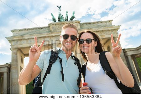 Happy Couple Making Peace Sign In Front Of Brandenburg Gate