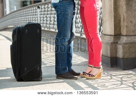 Low Section Of Couple Standing On Bridge With Luggage