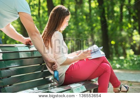 Man Stealing Mobile Phone While Woman Reading Book At Park