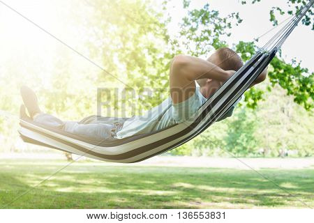Young Man Relaxing In Hammock At Park