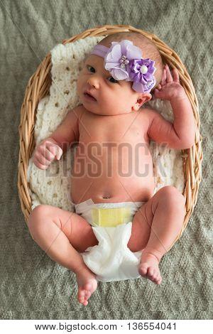 Baby Wearing Purple Headband Lying In A Wicker Basket