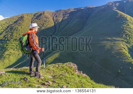 Girl traveling on mountains hills with backpack
