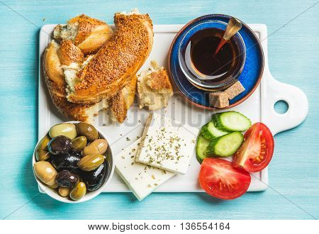 Turkish traditional breakfast with feta cheese, vegetables, olives, simit bagel and tea on white ceramic board over turquoise blue background. Top view