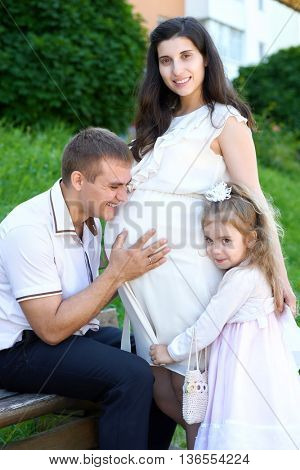 man and child listen belly of pregnant woman, happy family, couple in city park, summer season, green grass and trees