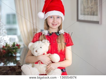 Little girl in Christmas hat against of Christmas tree hugging white bear
