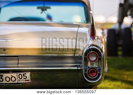MINSK BELARUS - MAY 07 2016: Close-up photo of beige Cadillac de Ville 1959 model year. Back view of retro classic vintage car. Shallow depth of field. Selective focus.