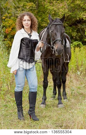 Woman with curly hair stands with bay horse in the park.