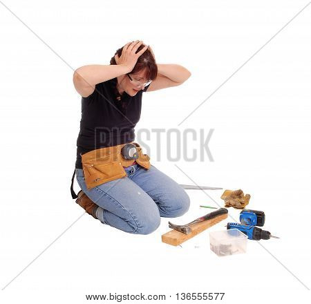 A woman kneeling on the floor isolated for white background is wondering what she did wrong with her work.