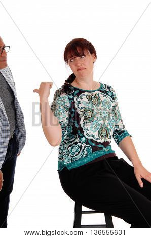 An upset woman sitting on a chair pointing back at her standing husband looking unhappy isolated for white background.