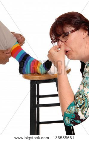 A discussed woman holding her nose closed from the smell of her husband's socks isolated for white background.