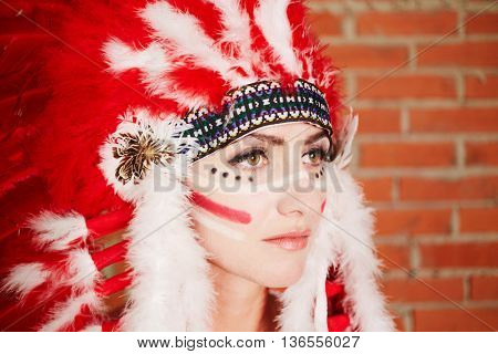 Closeup portrait of young woman dressed in hat made of red and white feathers.