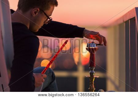 Young man adjusts cap of hookah sitting in armchair on highrise roof at sunset dusk.