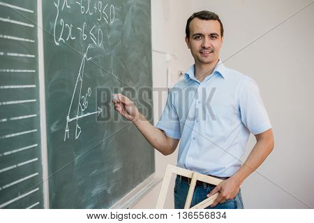 Young teacher or student holding triangle pointing at chalkboard with formula, looking to camera and smiling.