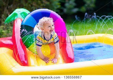 Children playing in inflatable baby pool. Kids swim and splash in colorful garden play center. Happy little boy playing with water toys on hot summer day. Family having fun outdoors in the backyard.