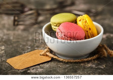 Homemade macarons served in a small bowl.