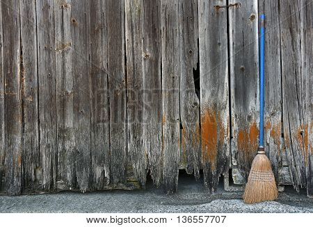 old used broom leaning on weathered barn wood siding