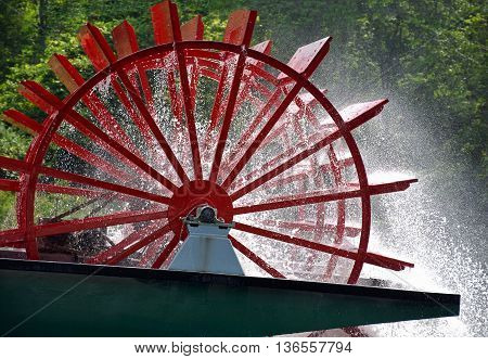 Red paddle wheel on vintage river boat spraying water.
