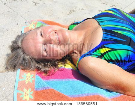 Mature female blond beauty relaxing on the beach outdoors.