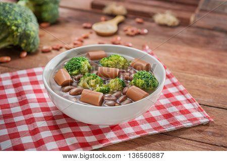 Bowl of soup with peanut cauliflower and sausage on the table in restaurant