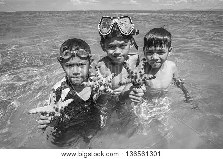 SABAH MALAYSIA - NOVEMBER 19: Unidentified Bajau Laut kids hold a beautiful starfish at Maiga Island on November 19 2015.