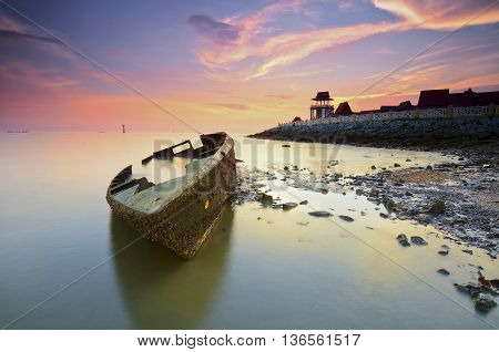 Scenery of stranded ship with pieces of ship part silhouette and vibrant sunset sky. Soft focus and some motion blur due to long exposure.