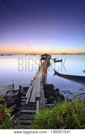 Blue hour scenery of old abandoned fisherman jetty before sunrise.