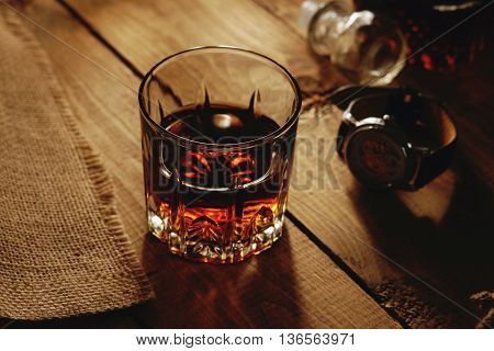 Glass of whiskey and wristwatch on a table