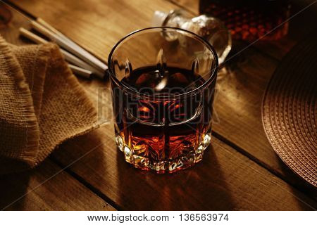 Glass of whiskey, cigaretes and hat on a table