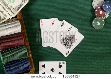 Cards with poker hand with chips and money on a green background