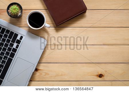 Top view office stuff with labtop cup of coffee and leather notebook with workspace.Flat lay image