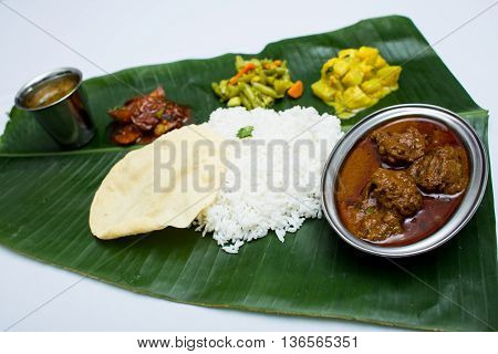 Indian mutton with plain rice on banana leaf tray