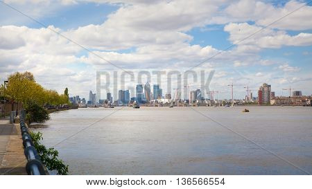 London, UK - May 4, 2015: Canary Wharf distant view from the River Thames. View includes O2 London arena, known as millennium dome