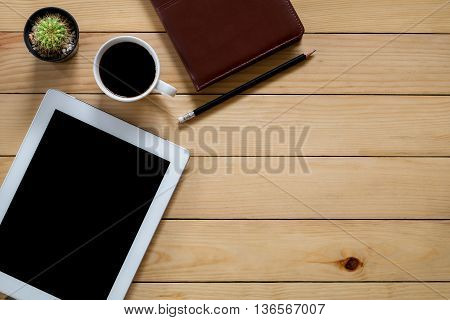 Office stuff with blank screen tablet leather notebook pencil and cup of coffee.Top view with workspace. flat lay image.