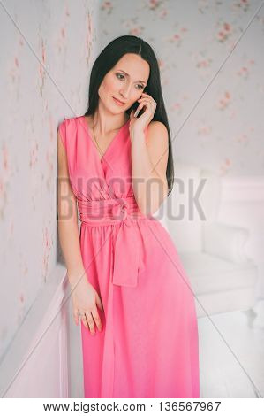 Young woman in rose dress mobile phone talking. Smartphone call. Girl smail and talk with cellphone