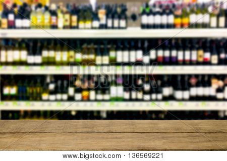 Wine liquor bottle on shelf blurred background with empty wooden top table. For product display