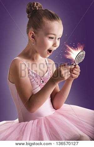 Ballerina children dancer in pink tutu looking in the magic mirror