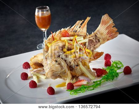 Hong Kong Style fried Tilapia fish on white plate