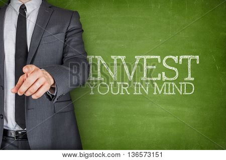 Invest in your mind on blackboard with businessman finger pointing