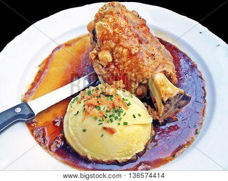 Crispy German pork knuckle with big scoop of mash potato