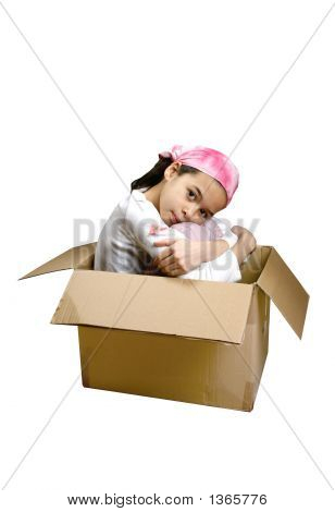 A Little Girl Sitting In A Box, Isolated On White.