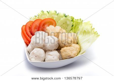 Fish balls with sliced tomato and cucumber on white bowl