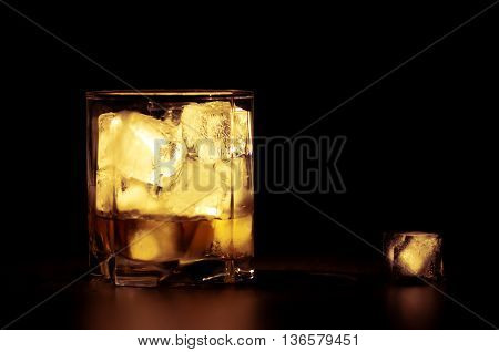Whiskey with ice cubes in warm tones