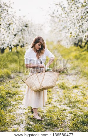 Beautiful young woman with a basket in blooming spring garden