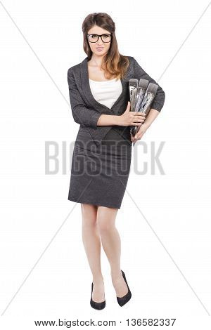 Businesswoman in business suit holding folders on white
