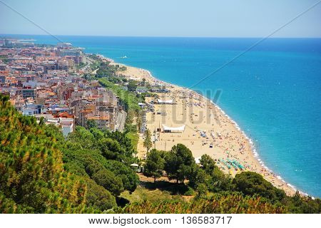 panoramic view from the mountains to the Spanish city by the sea, beautiful wide beach, a strip of coniferous trees, pine trees, low houses with orange roof, beautiful blue, blue sea