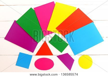 Multicolored cardboard geometric shapes. Cut from color cardboard triangle, square, oval, trapezoid, rectangle, circle. Kids education concept. Sheets of colored paperboard on white a wooden table
