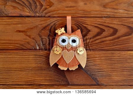 Brown felt owl decorated with heart and buttons in the shape of flowers and butterfly. Home decor for Valentine's day, birthday. Cute soft owl isolated on brown wooden background