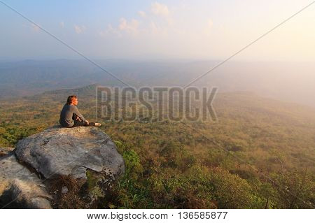 Adult tourist in black trousers jacket and dark cap sit on cliff's edge and looking to misty hilly valley bellow